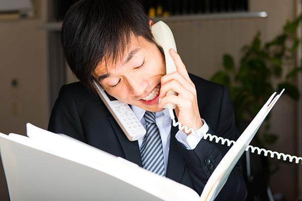 社内で電話する男性