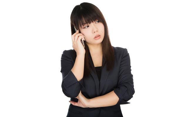 電話で問い合わせる女性
