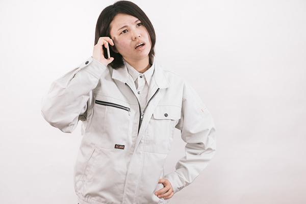 電話をかける作業着の女性