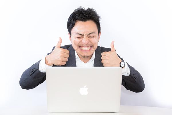 パソコンの前で喜ぶ男性